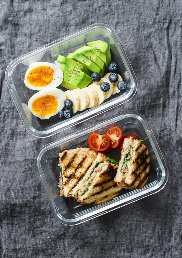 Dwa lunchu zdrowy biurowy pudełko z cukierki i pikantnym jedzeniem Gotowany jajko, avocado, tuńczyków szpinaków ser ściska i owoc obraz royalty free