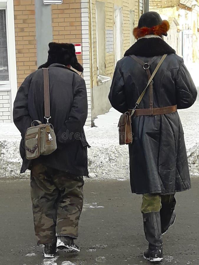 Dwa mężczyzny chodzi w dół ulicę w starej rewolucyjnej odzieży, retro styl Zima, Rosja zdjęcia stock