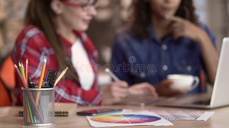 Dwa młodego projektanta przegląda nową odzieżową kolekcję na laptopie i robi notatkom fotografia stock