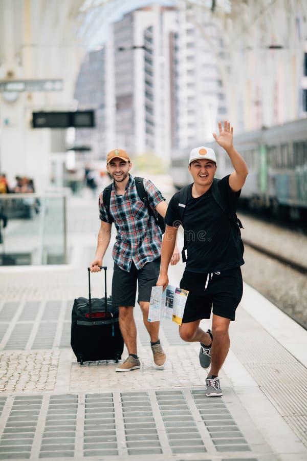 Dwa mężczyzn podróżnika chybienie po pociągu na platformie na stacji kolejowej lub opóźniony na pociągu i bieg samochodowej miast zdjęcie stock