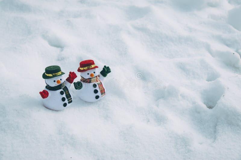 Dwa mężczyzna Śnieżny stojak wśród stosu śnieg w parku Światło słoneczne jest warmi fotografia royalty free