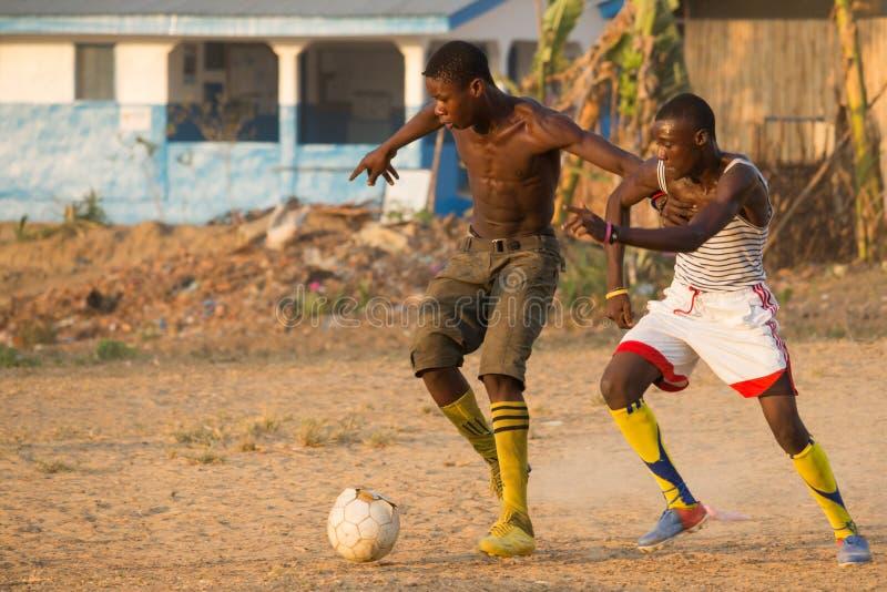 Dwa mężczyzna bawić się piłkę nożną w Afrykańskiej wiosce obraz stock