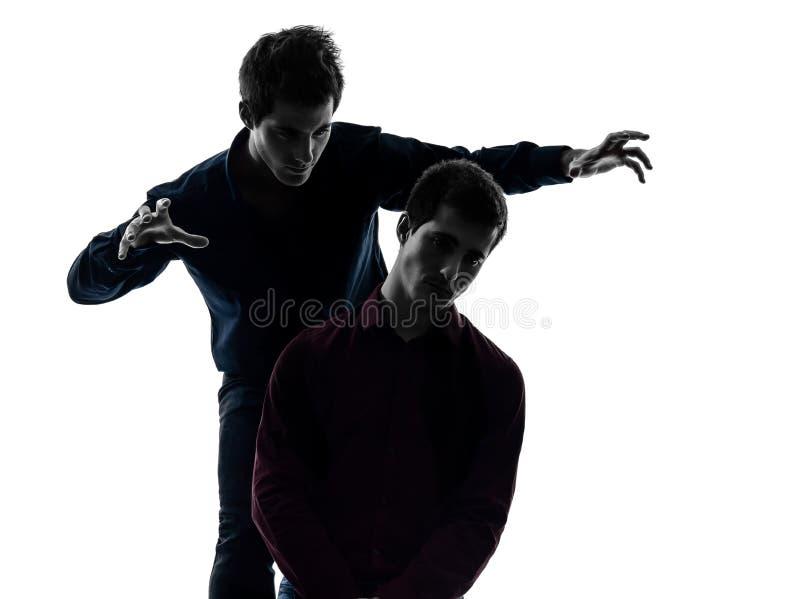 Dwa mężczyzna brat bliźniak przyjaciół dominaci pojęcia sylwetka obraz stock
