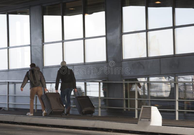 Dwa mężczyzna chodzi z trolly ` s na Jan Schaefer przerzucają most Amsterdam holandie obrazy royalty free