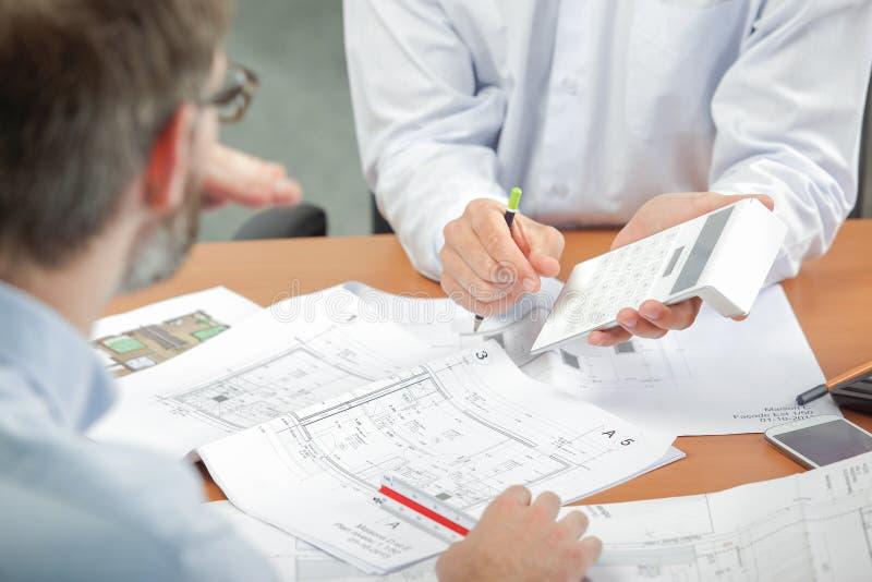 Dwa mężczyzna dyskutuje projekty trzyma kalkulatora zdjęcia stock