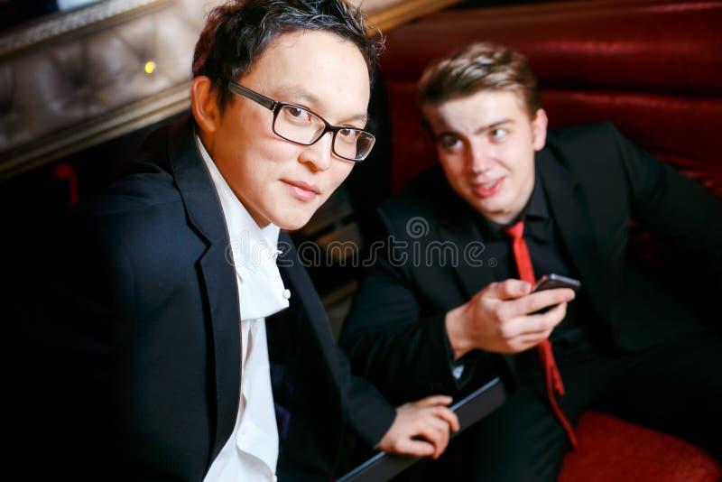 Dwa mężczyzna elegancki opowiadać, ubieraliśmy kostiumy i krawaty, nieformalna atmosfera przy barem, mężczyzna przyjaźń zdjęcia stock