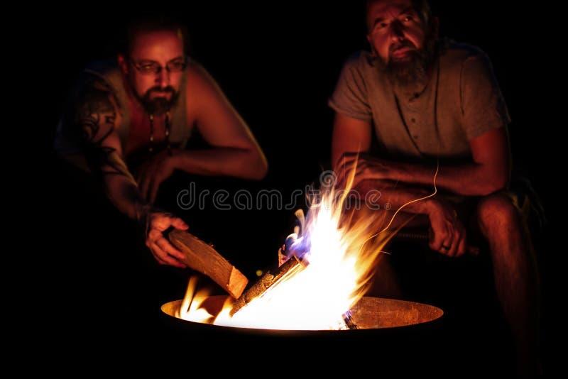 Dwa mężczyzna siedzi na ogieniu, ognisko na grabie przy nocą, out obrazy royalty free