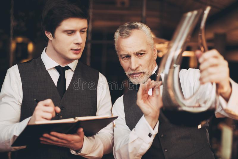 Dwa mężczyzna sommelier smaczny wino w restauracyjnym patrzeje dekantatorze z winem fotografia royalty free