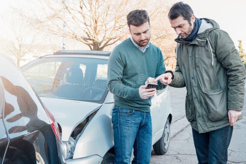 Dwa mężczyzna używa telefon komórkowego po kraksy samochodowej zdjęcie royalty free