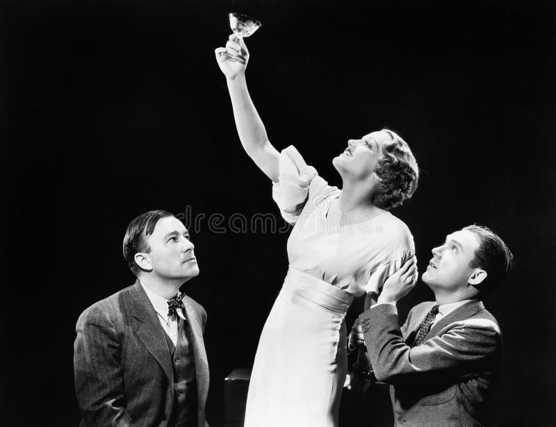 Dwa mężczyzna wspiera kobiety podnosi jej wina szkło (Wszystkie persons przedstawiający no są długiego utrzymania i żadny nieruch zdjęcia royalty free