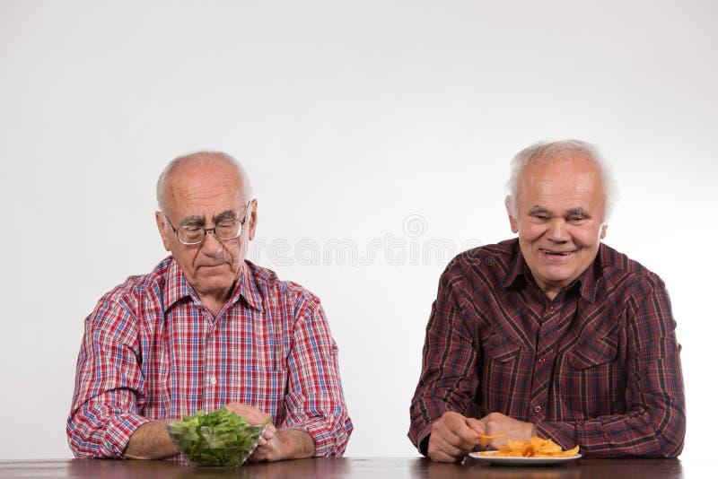 Dwa mężczyzny z zdrowym i szybkim żarciem fotografia stock