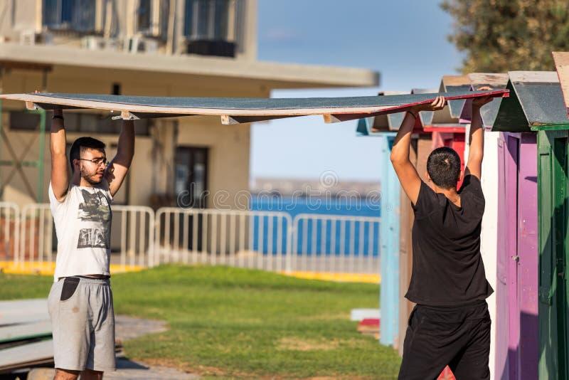 Dwa męskiego pracownika - cieśle gromadzić dach sklejkowe kabiny w Heraklion, Grecja fotografia stock