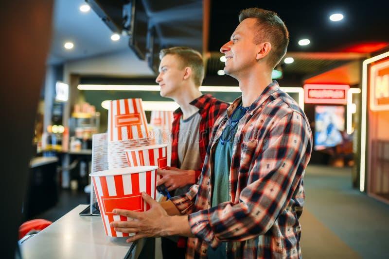 Dwa męskiego przyjaciela kupuje popkorn w kino barze obrazy stock