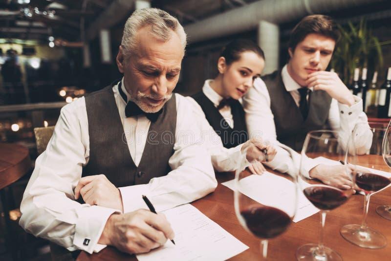 Dwa męskiego sommeliers i żeńskiego sommelier uzupełniali wino listy obsiadanie przy stołem z szkłami wino obraz stock