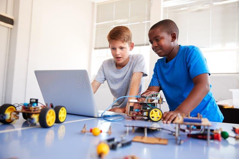 Dwa Męskiego ucznia Buduje robota pojazd I Programuje Wewnątrz Po Szkolnej Komputerowej cyfrowanie klasy zdjęcia stock