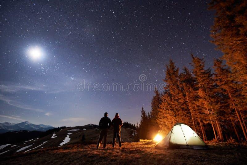 Dwa męskiego wycieczkowicza odpoczynek w jego obozie blisko lasu przy nocą pod pięknym nocnym niebem gwiazdy i księżyc pełno zdjęcie stock