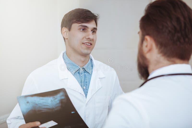 Dwa męskiej lekarki dyskutuje promieniowanie rentgenowskie skanują przy szpitalem zdjęcia royalty free