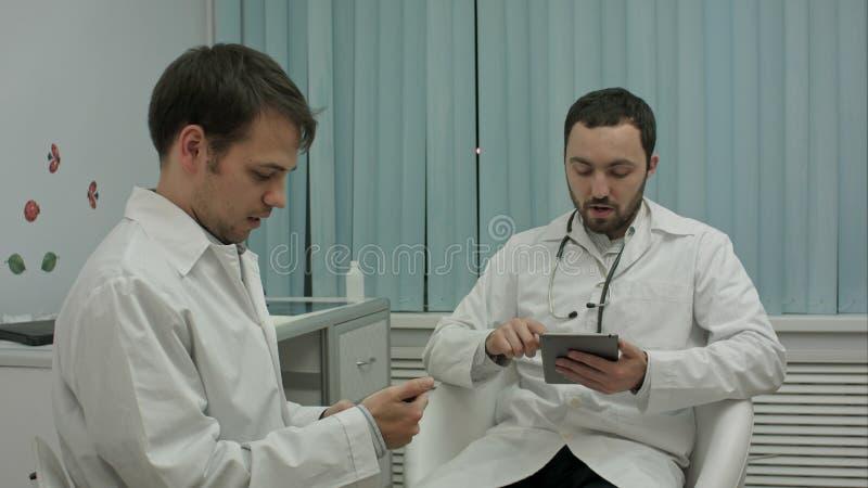 Dwa męskiej lekarki przy medycznym gabinetem używa telefony komórkowych obraz royalty free