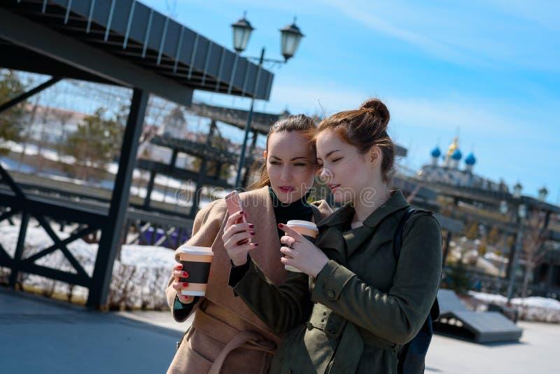 Dwa młoda kobieta podróżnika w żakiecie na odprowadzeniu na ulicach Kazan, używają smartphone z nawigatorem zdjęcie stock