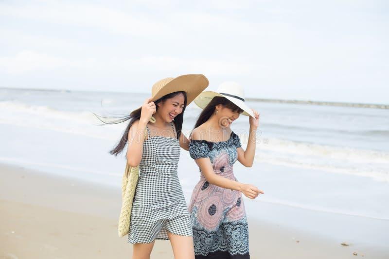 Dwa młoda kobieta przyjaciela śmia się i chodzi na plaży fotografia stock