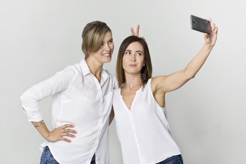 Dwa młoda kobieta w biały koszulowym mieć zabawę z robić selfie Przeciw biały tłu pracowniany strzał obrazy royalty free