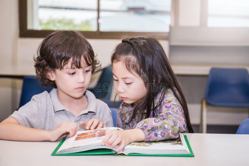 Dwa młode dziecko czytelniczej książki przy szkolną biblioteką obrazy royalty free