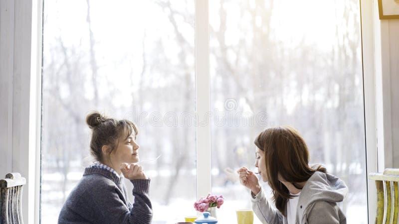 Dwa młodego żeńskiego przyjaciela je herbaty w kawiarni i pije obraz stock