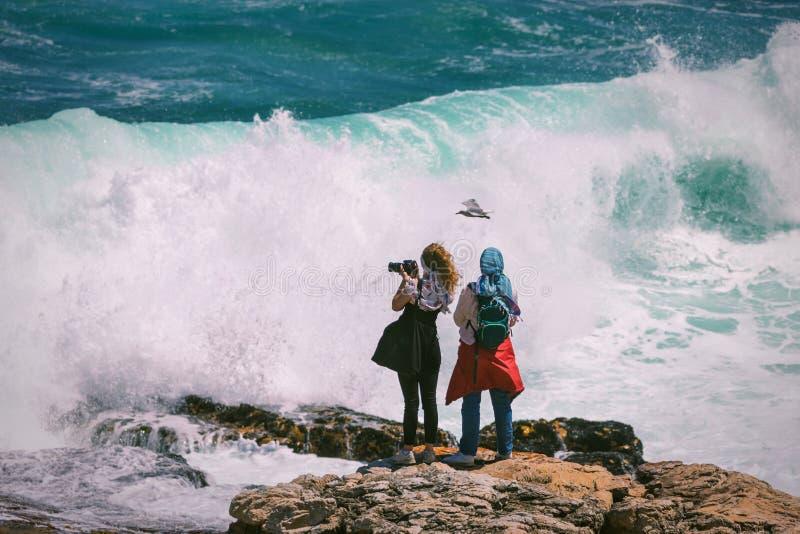 Dwa młodego żeńskiego turysty stawia czoło ogromną niebezpieczną falę i fotografuje obrazy stock