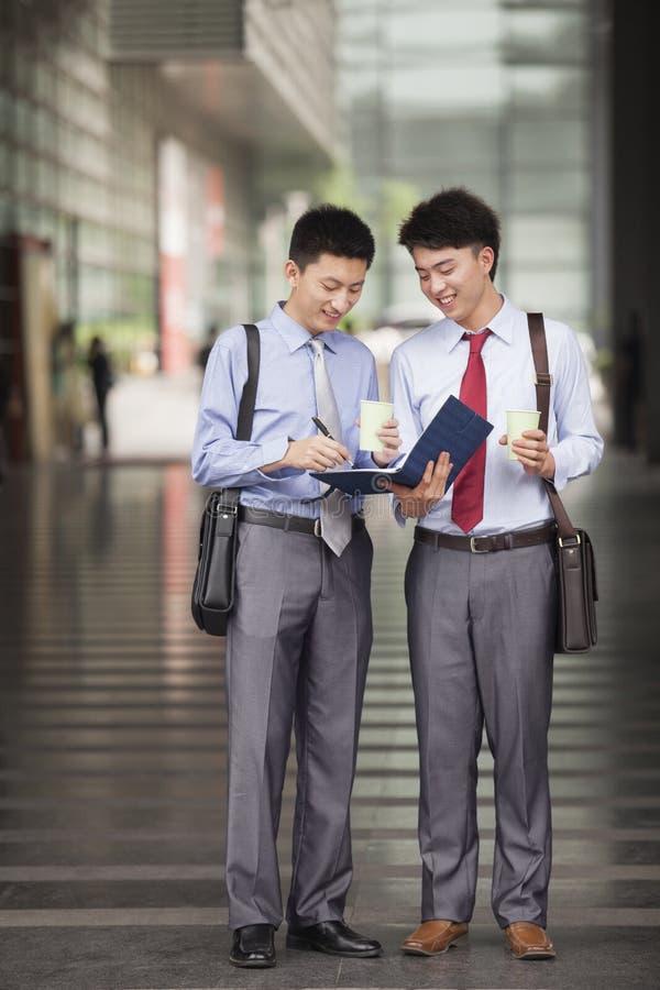 Dwa młodego biznesmena ono uśmiecha się, stoi i pracuje, outdoors fotografia royalty free