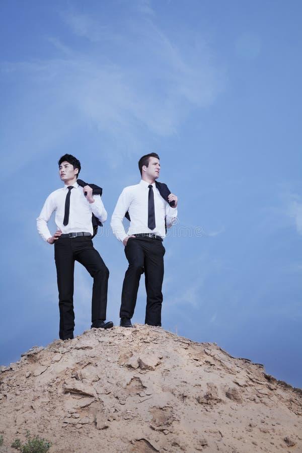 Dwa młodego biznesmena stoi na wierzchołku wzgórze w pustyni fotografia stock