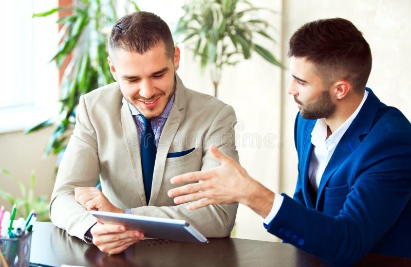 Dwa młodego biznesmena używa touchpad przy spotkaniem obraz stock