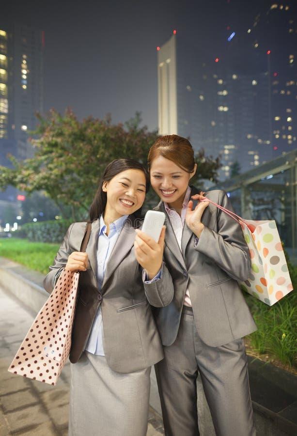 Dwa Młodego bizneswomanu uśmiecha się obrazek one z telefonem komórkowym i bierze zdjęcia royalty free