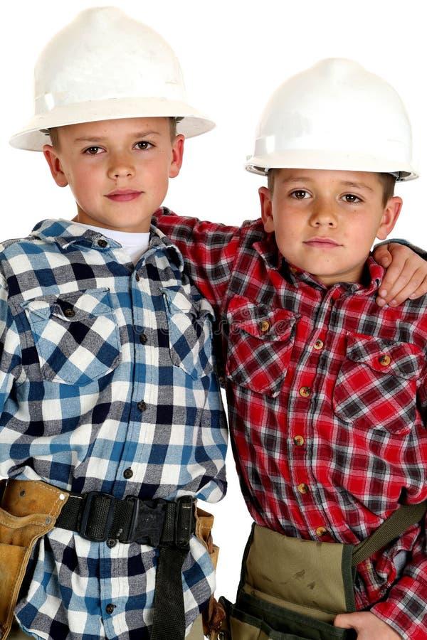 Dwa młodego brata jest ubranym hardhats i narzędzie pasków ściskać zdjęcia stock