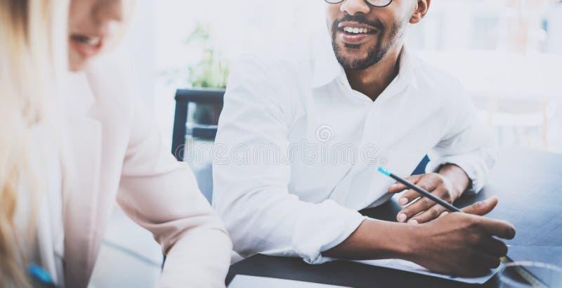 Dwa młodego coworkers pracuje wpólnie w nowożytnym biznesowym projekcie Obsługuje uśmiechać się szkła i być ubranym, robi prac no zdjęcie stock
