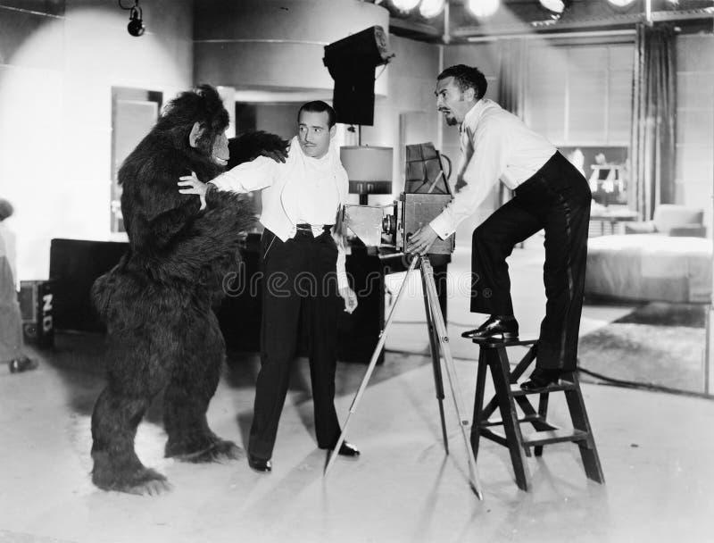 Dwa młodego człowieka patrzeje bojącym się atakującego gorylem (Wszystkie persons przedstawiający no są długiego utrzymania i żad zdjęcia royalty free