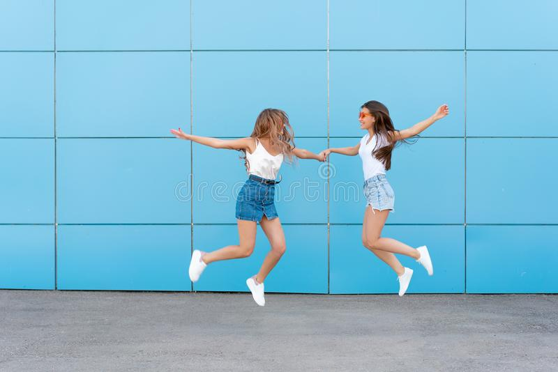 Dwa młodego modniś kobiety przyjaciela stoi i ono uśmiecha się nad błękit ścianą w retro neonowych okularach przeciwsłonecznych obraz stock