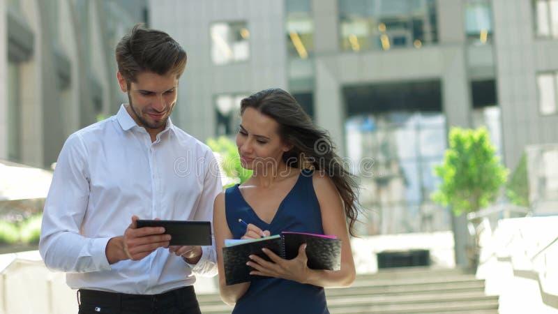 Dwa młodego partnera biznesowego pracuje na ulicie Partnery biznesowi dyskutuje dokumenty i pomysły stoi przed, obraz royalty free