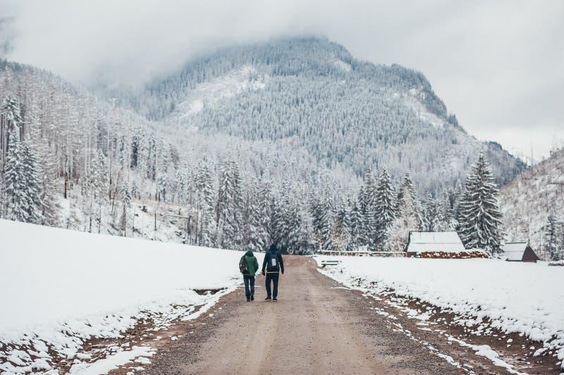 Dwa młodego podróżnika mężczyzny z plecakami chodzą śnieżną drogę w zima sezonie Tatrza?skie g?ry widok z powrotem fotografia royalty free