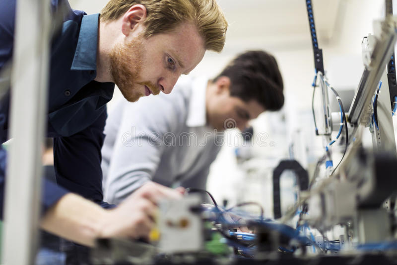 Dwa młodego przystojnego inżyniera pracuje na elektronika składnikach zdjęcie royalty free