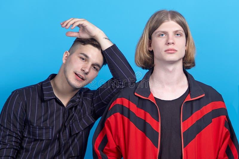 Dwa młodego przystojnego mężczyzny, ono uśmiecha się Homoseksualna związku lub zakończenia przyjaźń Jeden z blondynem inna jeden  obrazy stock