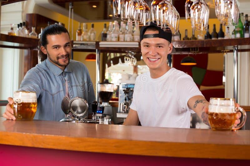 Dwa młodego rozochoconego szczęśliwego barmanu oferuje piwo klienci zdjęcia royalty free