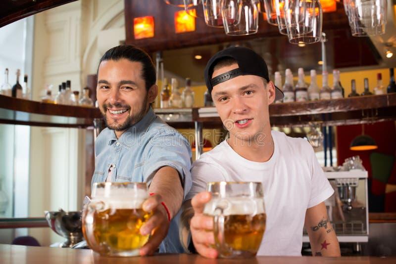 Dwa młodego rozochoconego szczęśliwego barmanu oferuje piwo klienci obrazy royalty free