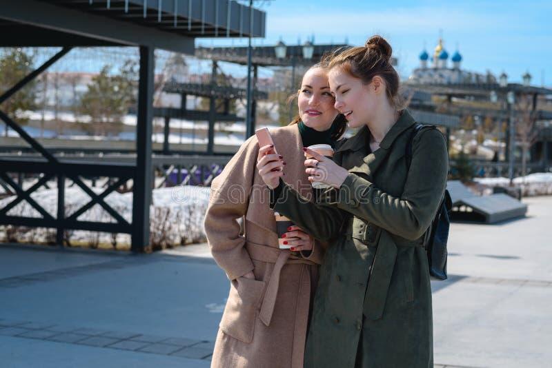Dwa młodego studenckiego podróżnika w żakiecie na odprowadzeniu na ulicach Kazan, używają smartphone z nawigatorem fotografia stock