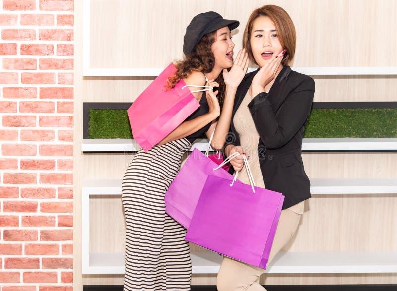 Dwa m?odego szcz??cia dziewczyny azjatykciego przyjaciela z toreb na zakupy opowiada? obraz royalty free