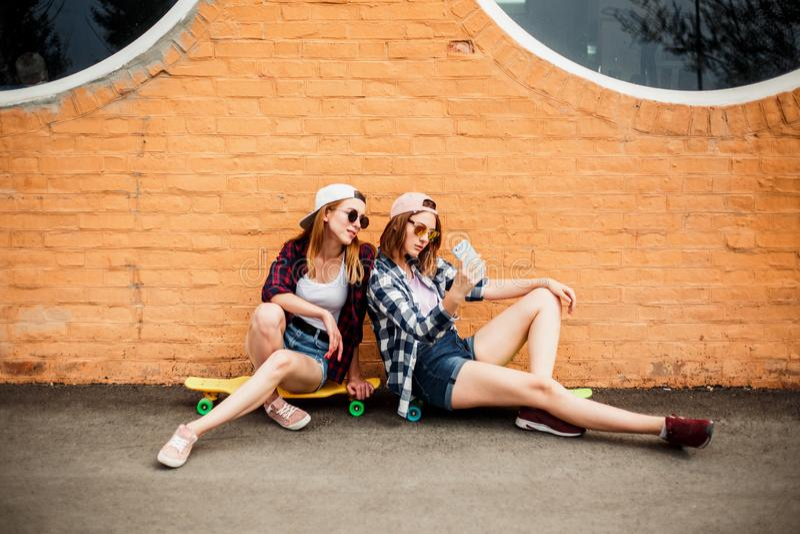 Dwa młodego szczęśliwego dziewczyna przyjaciela w modnisia stroju obsiadaniu na longboards i robić selfie na telefonie fotografia royalty free