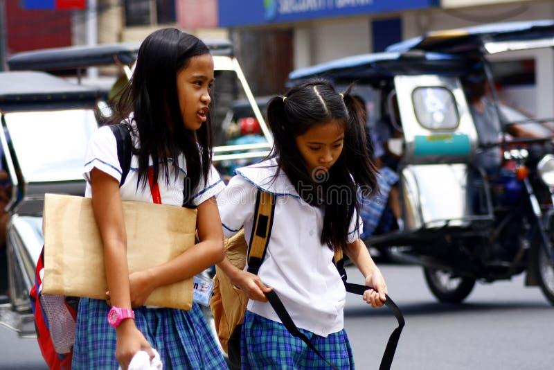 Dwa młodego ucznia gawędzą podczas gdy chodzący na ich sposobie szkoła fotografia royalty free