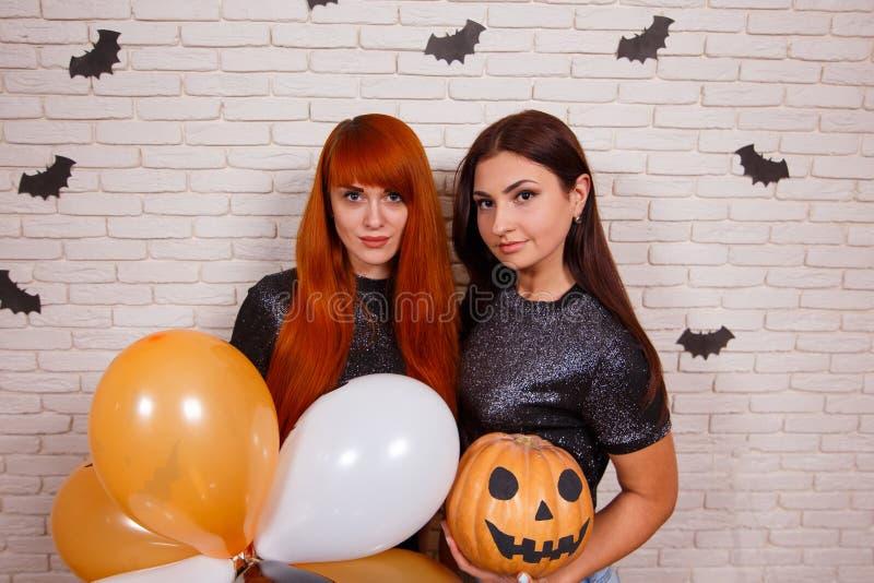 Dwa młodej ślicznej kobiety z dyniowym i stubarwnym balonu havi zdjęcia stock