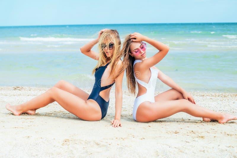Dwa młodej atrakcyjnej dziewczyny z długie włosy w swimsuits relaksują na plaży w morzu obrazy royalty free