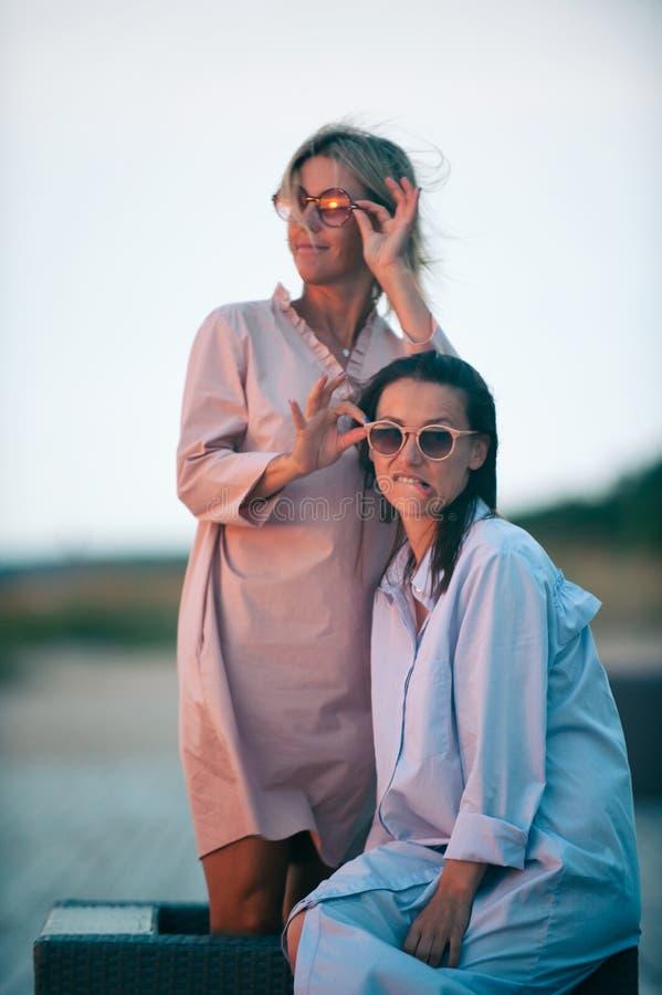 Dwa młodej atrakcyjnej kobiety odpoczywa wpólnie na plaży przy zmierzchem zdjęcie royalty free