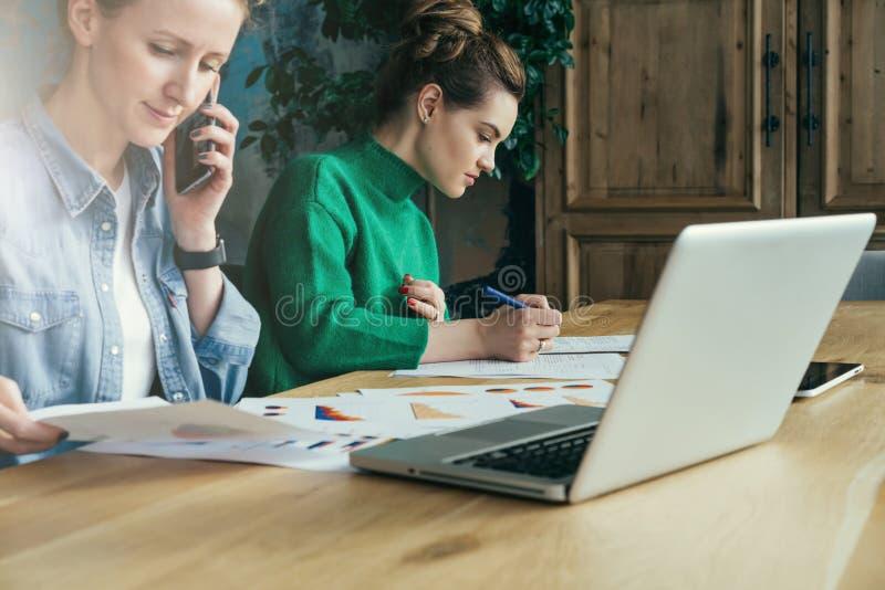 Dwa młodej biznesowej kobiety siedzi w biurze przy stołem i pracą wpólnie Na stołowych laptopu i papieru mapach obraz stock